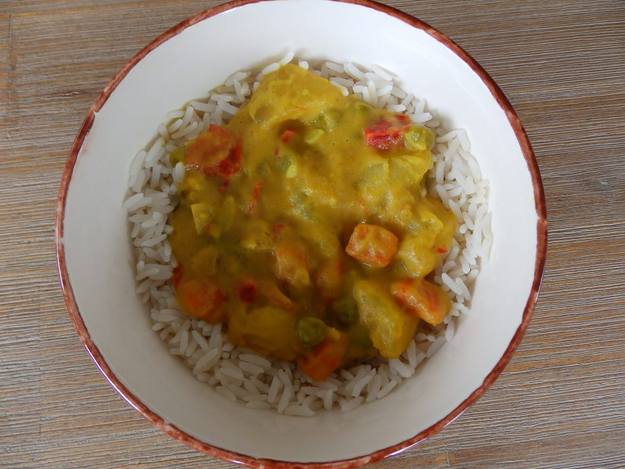 Un curry de pommes de terre et autres légumes (poivron, carottes, petits pois)
